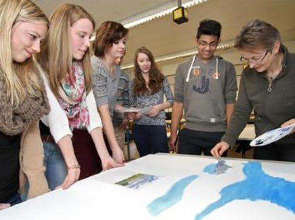 Kunstlehrerin Hanna Matthäus erklärt den Schülern, wie sie mit dem Palettmesser umgehen müssen.