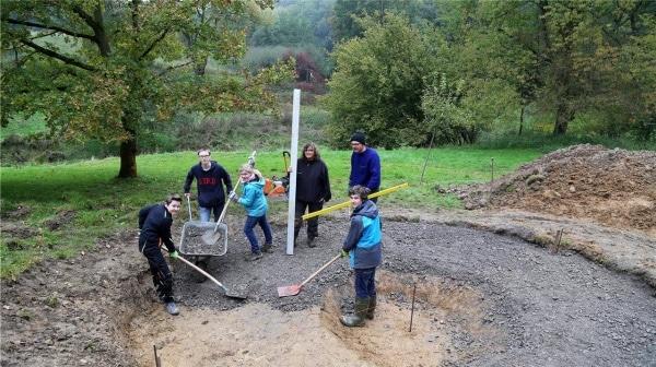 Eine Gruppe richtet den Feuerplatz im MINT-Forscher-Park her. Der Platz wird geschottert und gepflastert.